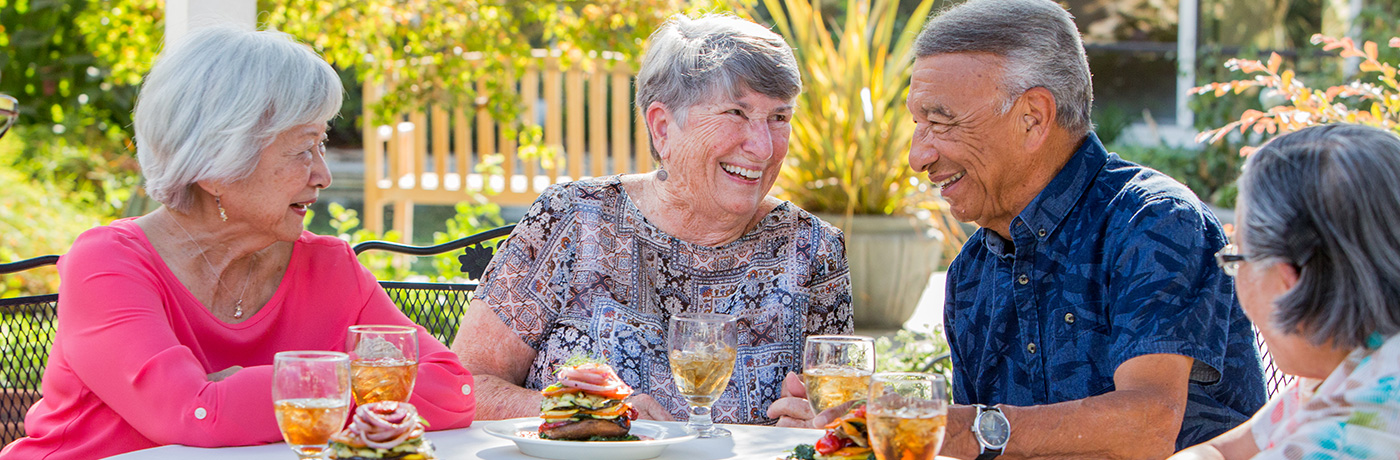 Residents of O'Connor Woods enjoying a meal together on the patio.