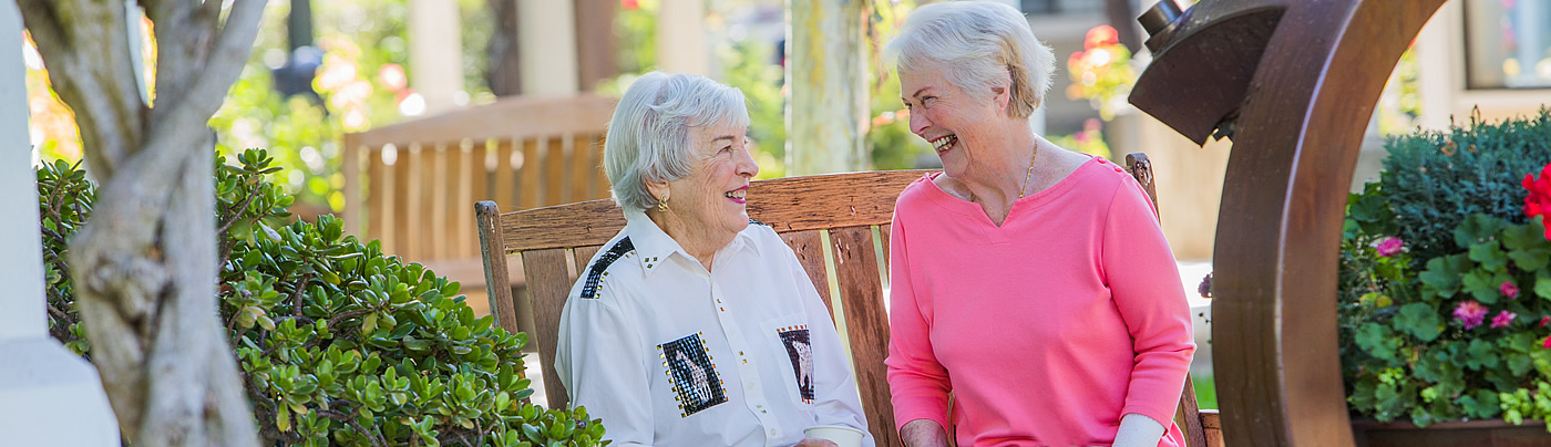 Two women sitting on a bench laughing